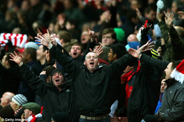Jubilation: Arsenal fans celebrate as they watch their side stroll to victory over their North London rivals