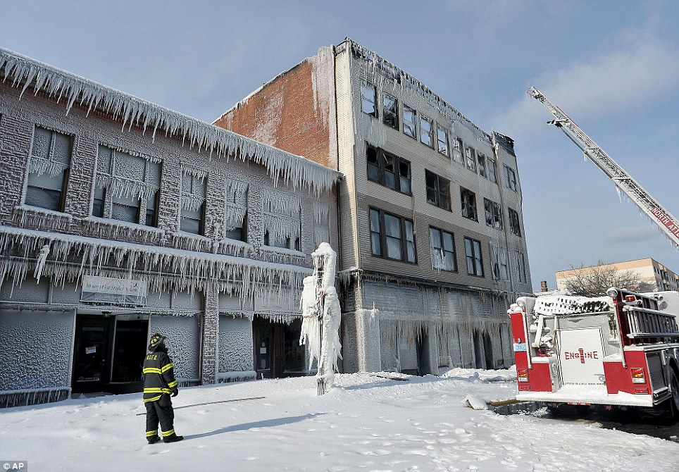 Frozen: A firefighter surveys the former Odd Fellows Building in downtown North Attleboro, Mass., Friday, Jan. 3, 2014, after it was destroyed in an early morning multi-alarm fire