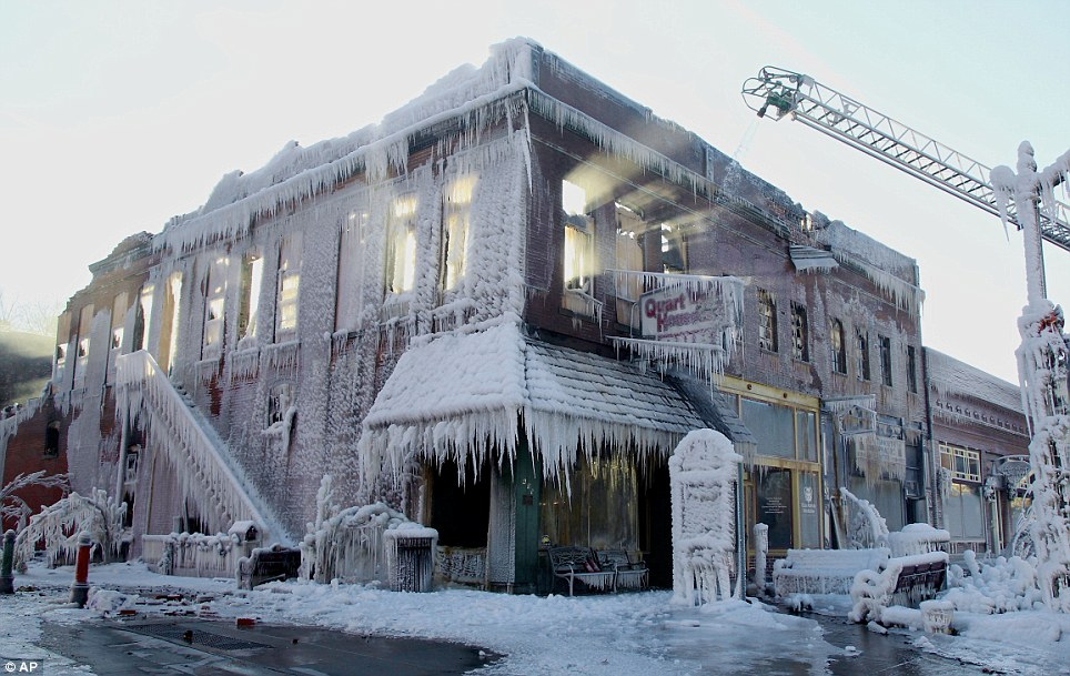 Shards: Sunlight streams through the windows of a building which caught on fire in Plattsmouth, Neb., Friday, Jan. 3, 2014, and the water sprayed on it by fire fighters froze