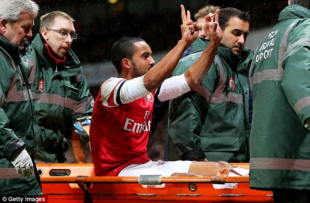 Cheeky: Theo Walcott was injured late on in the 2-0 win over Spurs and teased their supporters as he made his way around the pitch on a stretcher