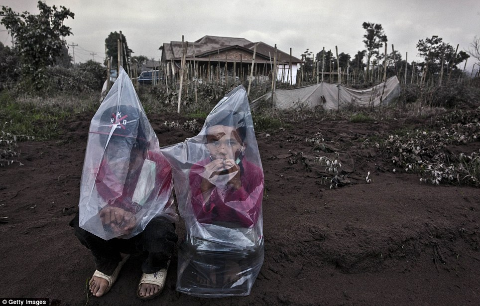 Children take shelter under plastic covers in Tiga Pancur, North Sumatra. The volcano spurted gas, rocks and lava which landed up to four miles away