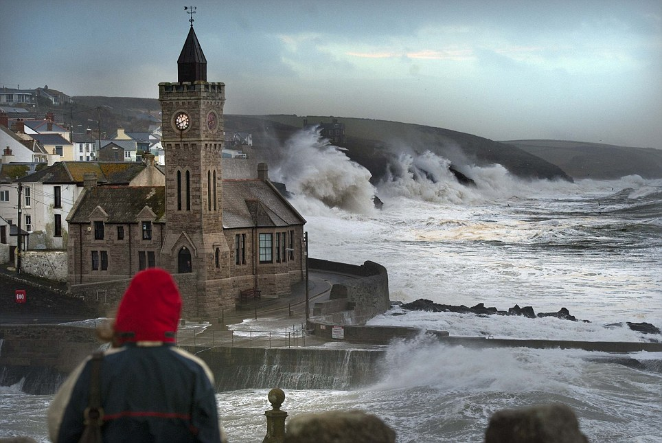 Crash: Porthleven in Cornwall today. The Met Office said bands of heavy showers would continue to move eastwards across parts of the UK