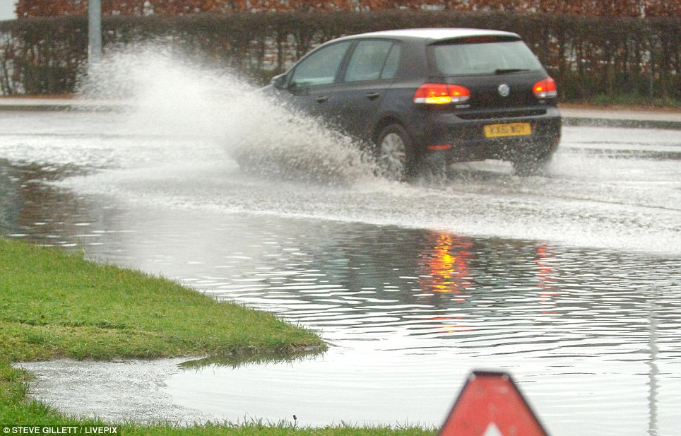 Carrying on: Road flooding alongside Epsom Downs Racecourse in Surrey. Prime Minister David Cameron pledged that lessons will be learned from the flooding