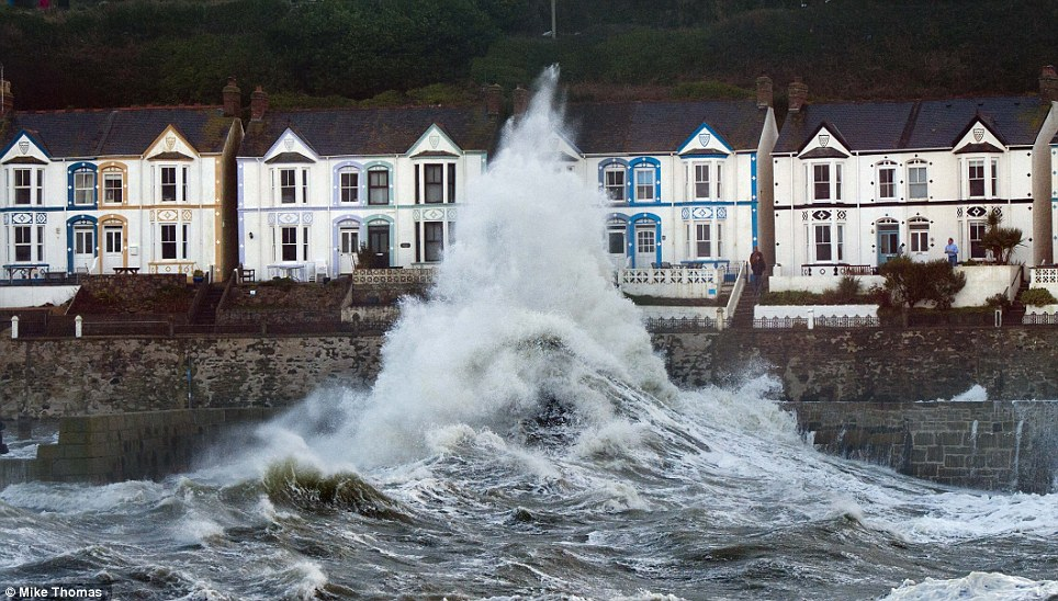 Forceful: A huge wave hits the harbour wall at Porthleven, clearing the houses. The EA estimates about 220 properties have been flooded so far