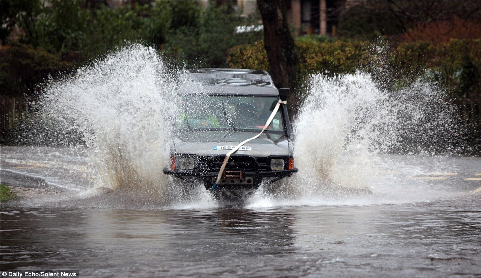 Trying to make it through: A 4x4 Land Rover splashes through the swollen ford at Brockenhurst in the New Forest, Hampshire, as flooding hits the South