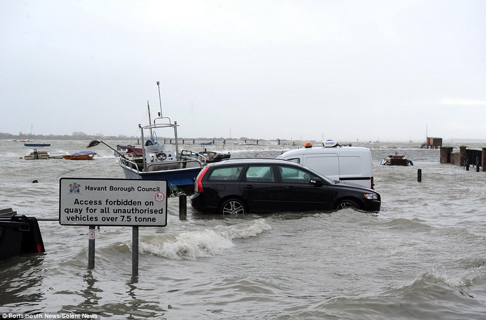 Where does the road end and the water begin? Flooding at Emsworth in Hampshire at high tide. Pictured is the South Street car park