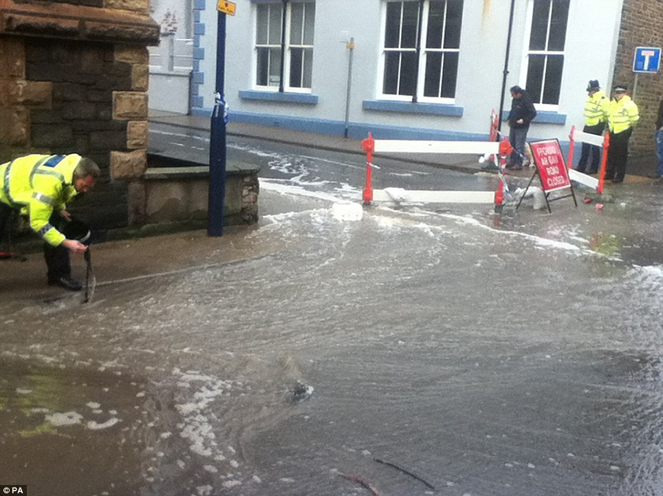 In the town: Police clear drains in Aberystwyth today as the seaside area braces itself for more storm damage