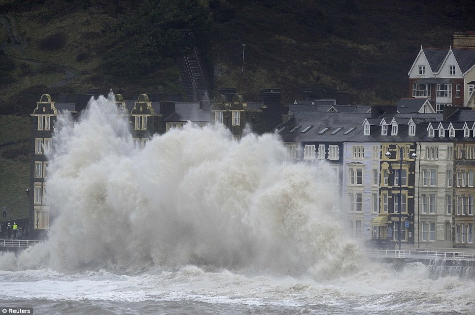 Evacuation ordered: Large waves crash over the promenade at high tide in Aberystwyth, Mid Wales