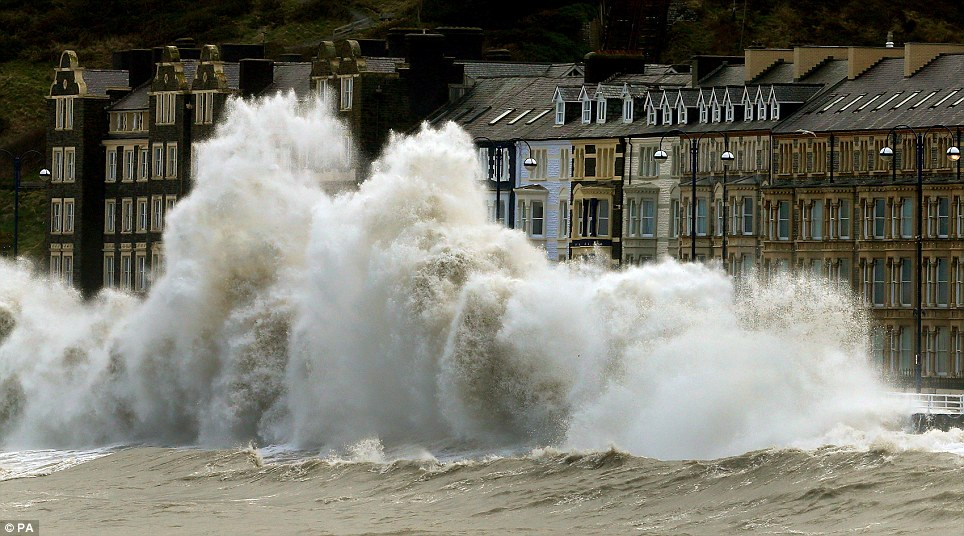Obscuring the promenade: Waves crash against the Aberystwyth coastline as strong winds and high tides continue to blow in from the west