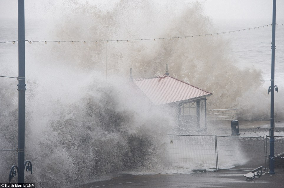 Already destroyed: At either side of the high tide at 11.20am today, a deep depression drives a huge ground swell of waves to crash into the promenade at Aberystwyth