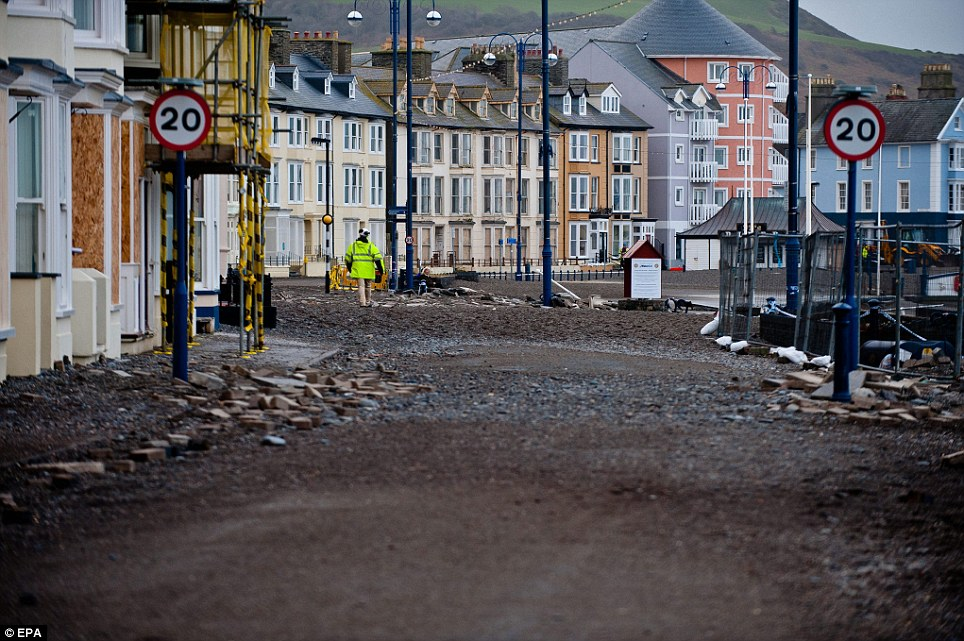 Disaster zone: A near-deserted sea front as local residents are advised to keep away while storm-driven giant waves batter the promenade of Aberystwyth