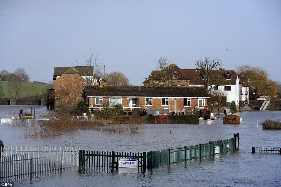 Submerged: A row of residential homes is surrounded by flood water in the town of Tewkesbury, Gloucestershire, as roads turn into rivers