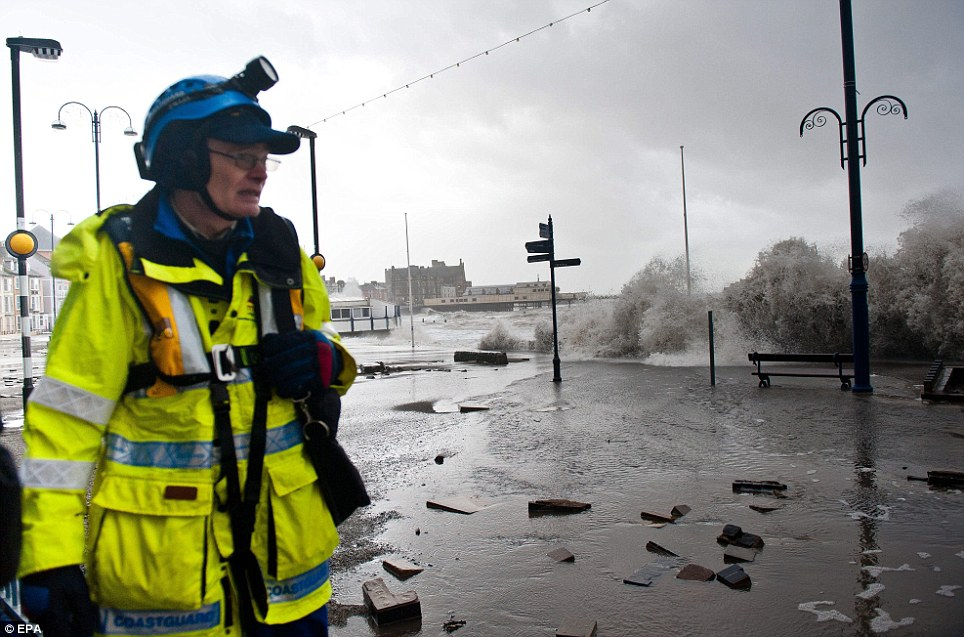 Looking on: A member of the local emergency services surveys the grim scene as storm-driven giant waves continue to batter the promenade in Aberystwyth