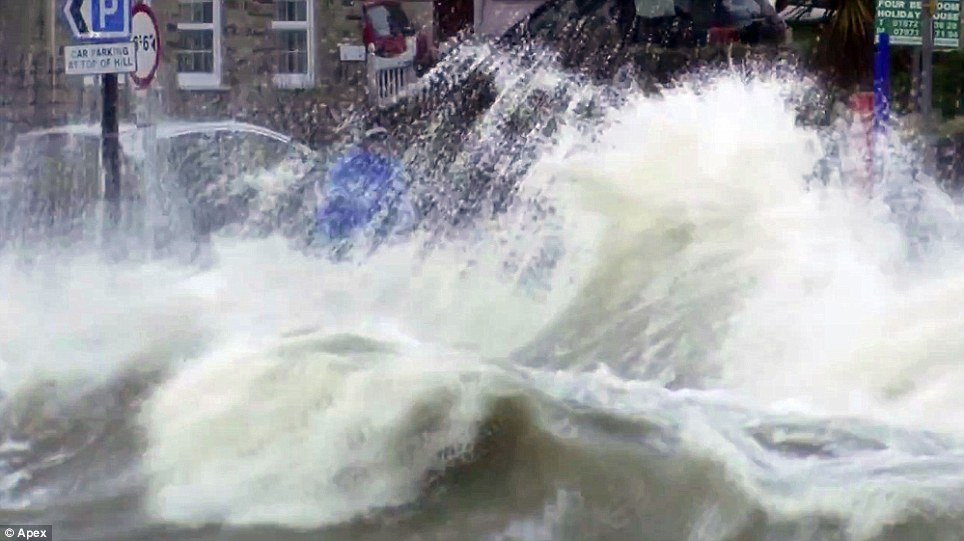 Splash: The pair and another man can be seen standing right on the edge of a slipway as an enormous wall of water is thrown up just feet away
