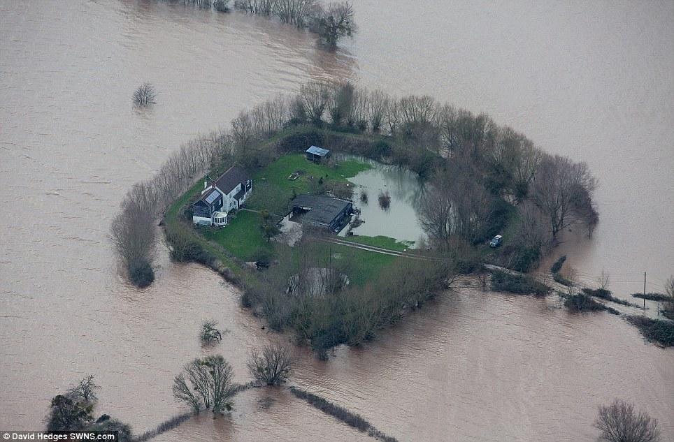 This house sits marooned in the middle of flood water after its homeowner ingeniously spent three years building a 6ft high clay bank to protect it