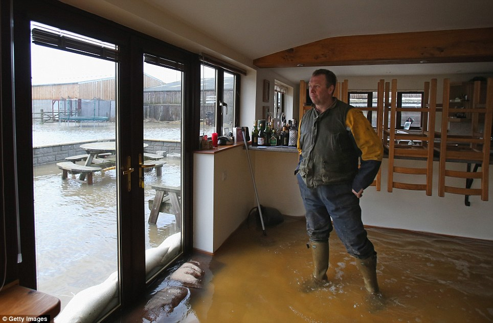 Muchelney resident and farmer Mike Curtis stands in his flooded kitchen in the village of Muchelney which has been cut off by flooding near Langport in Somerset