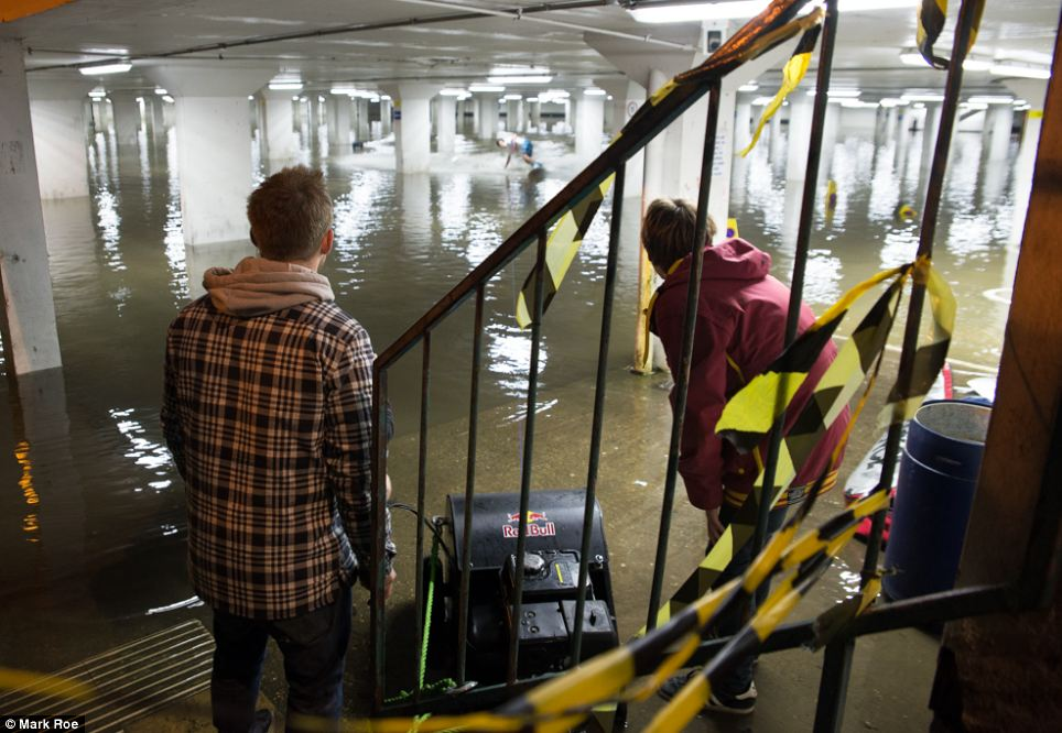 The boarders were pulled in over the 2ft-deep water in the Surrey carpark using a winch pulley system (pictured centre)