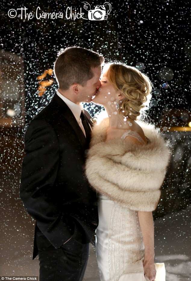 Braving the elements: Not even snow can stop this bride and groom from sharing a tender kiss