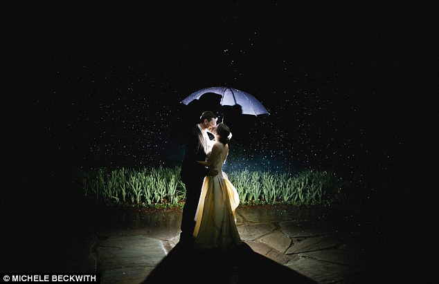 Magical: Lit by a spotlight and protected under their umbrella, the husband and wife in this image share a kiss in the dark outdoors as snowflakes fall around them, giving the illusion of stars