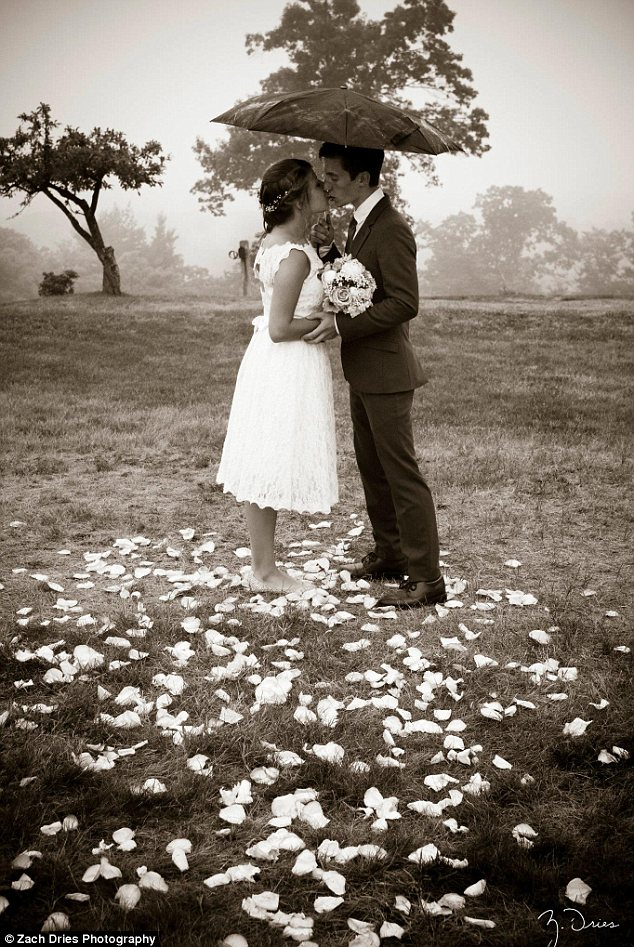 One love: A husband and wife brave the elements together as they hold hands in their dress and tuxedo, standing among rose petals and protected from the rain under a black umbrella