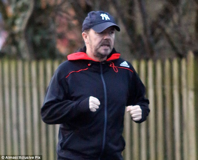 Fighting fit: The star pumped his fists as he jogged on the road in Hampstead , London, earlier this week