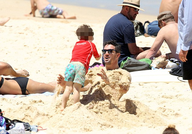 Up to his neck: Kevin Pietersen relaxing with son Dylan at Bondi Beach
