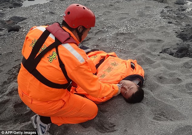 Safe: Members of the Taiwanese Coast Guard treated the 42-year-old after he was found lying on a beach 48 miles from where he had been swept away