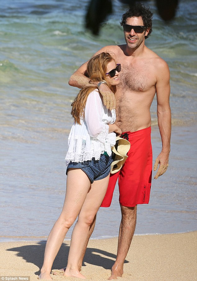 How cute! Isla Fisher and her husband Sacha Baron Cohen were seen cuddling on the beach in Hawaii on Monday