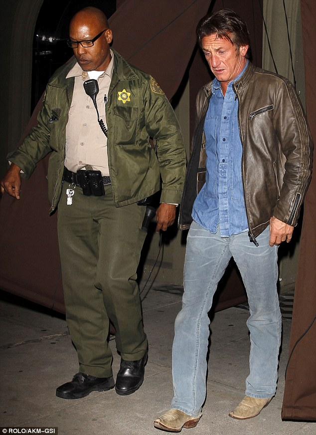 Helping hand: The actor appeared to have a police escort as he left Craig's restaurant the following day