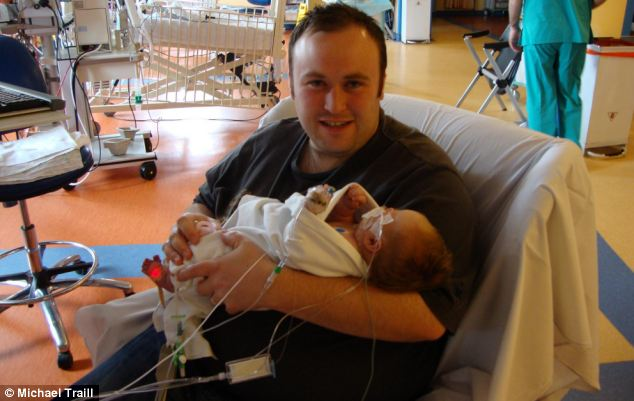 Hannah (pictured in hospital with her father, William) had to have life-saving hypothermia treatment after her birth - it saw medics reduce her body temperature to just 32C to prevent damage caused by a lack of oxygen
