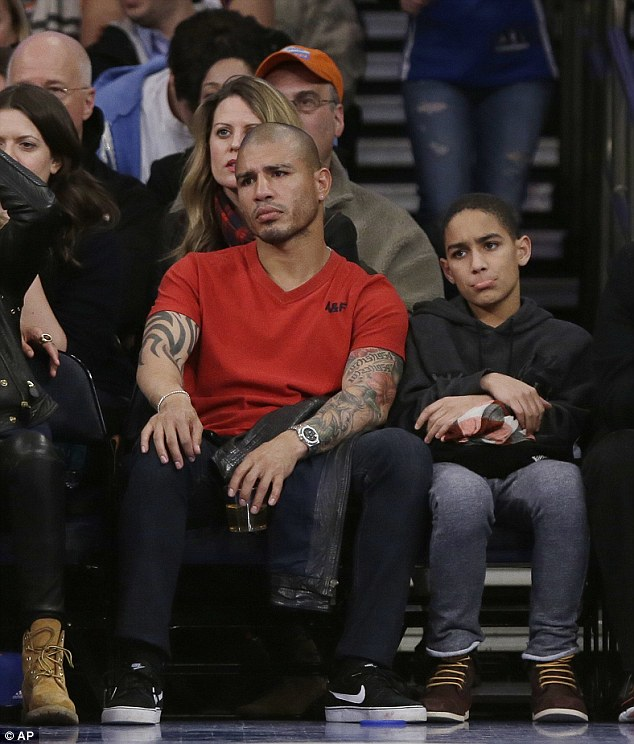 Absorbed in the action: Boxer Miguel Cotto looked a bit concerned as he watched the game unfold
