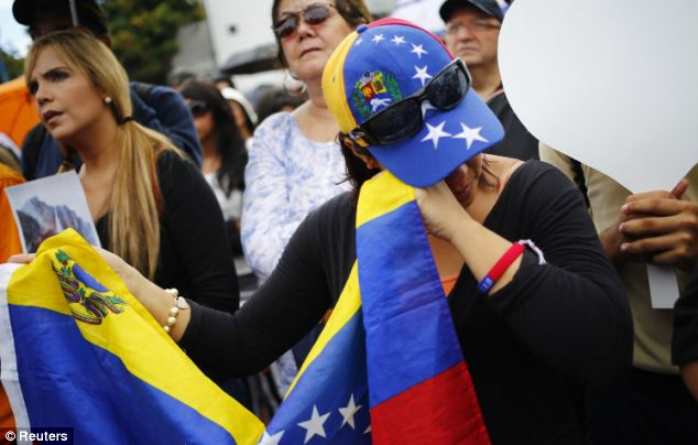 A fan of Monica Spear wipes away tears while taking part in the Caracas demonstration on Wednesday. Crowds gathered to protest the violence that has gripped the country