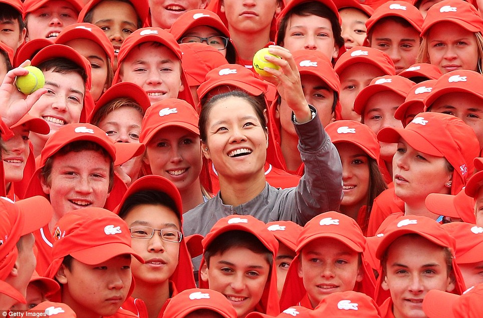 Life's a ball: Chinese tennis star Li Na, world number four, is welcomed at Melbourne Park by 380 red-capped ball boys ahead of the 2014 Australian Open