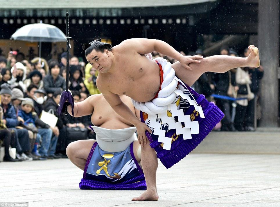 Hungry for success: Sumo Grand Champion Harumafuji Kohei performs the customary 'Dohyo-iri' (a ring purification ritual) during Dezuiri ceremony in Tokyo, Japan