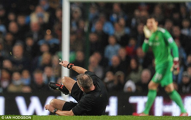 Man in the middle: Referee Jonathan Moss took a tumble after he slipped in the first half