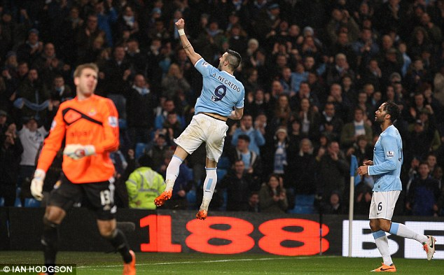 Jumping for joy: Negredo leaps in front of delighted City fans as 'The Beast' wraps up his hat-trick