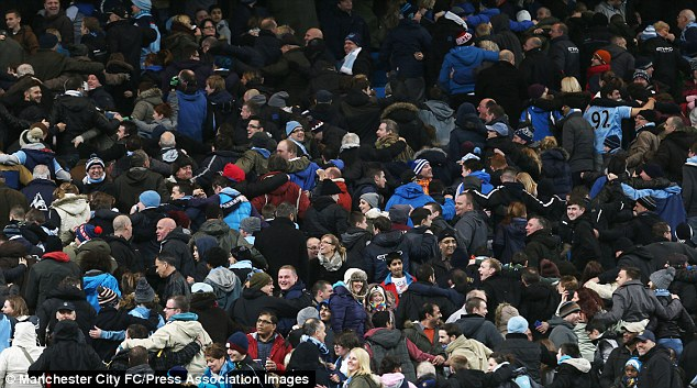 Turning the back: City fans celebrate with their famous 'Poznan' in the stands at the Etihad