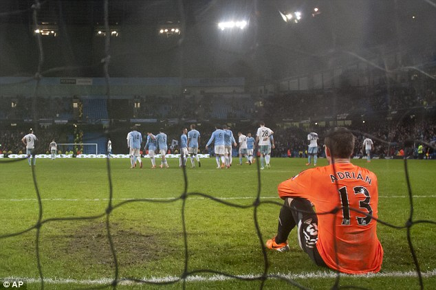 Hammered: Adrian sits on the turf as City players celebrate after Edin Dzeko netted his second of the night