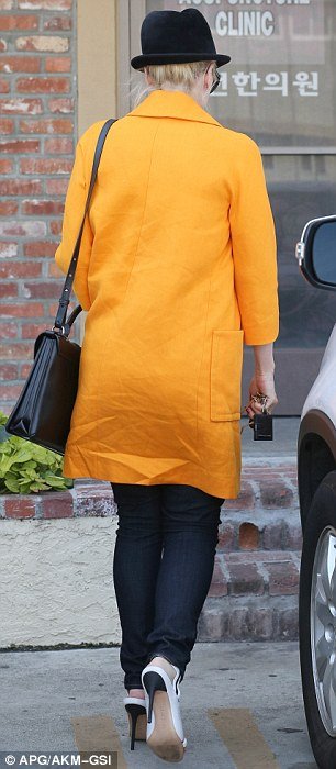 Can't miss her: For her day of being poked and prodded, the No Doubt front woman wore a pair of tight blue jeans with a simple long black tank covering her baby bump and a stand out long yellow trench