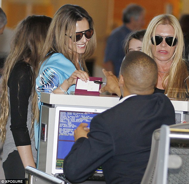 Beaming: Cheryl treated the check-in attendant to a wide smile as she handed over her passport