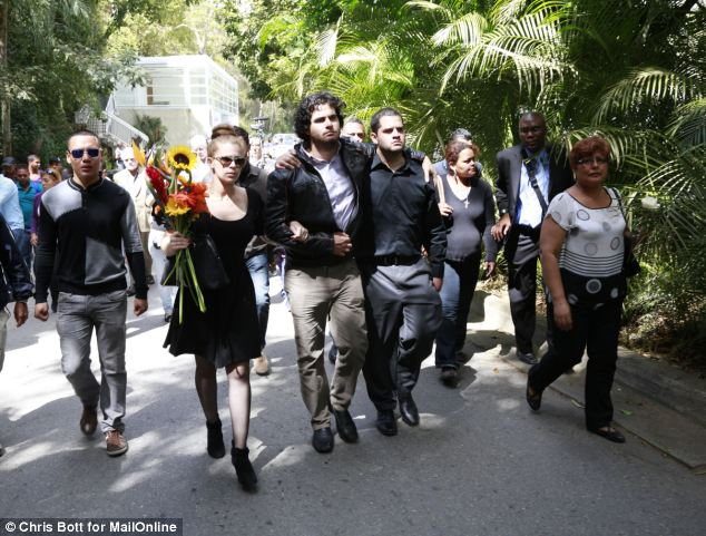 Long walk: Monica Spear's family accompany the coffins in Caracas today. The couple were buried side by side