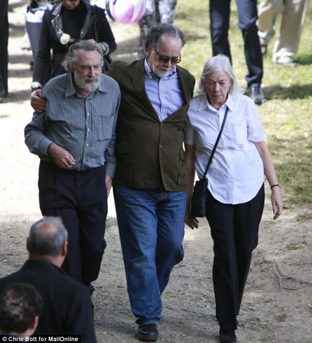 Support: Mr Berry's parents, Tom and Carol, are helped on their walk tot he graveside by a friend in the middle