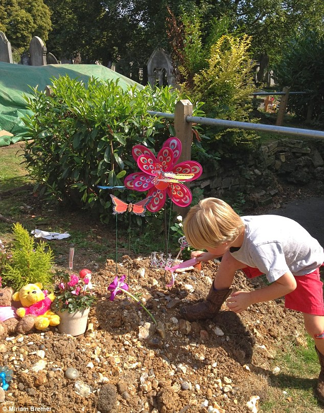 Tender: George with Lizzy at her grave. 'We buried her with her teddy, photos and cards, her sticker book and her comfort blanket,' says Miriam. 'We also made a memorial in our garden'