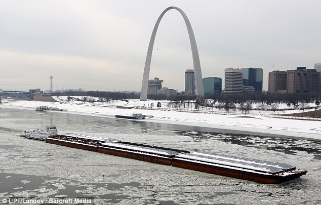 Barging through: A boat makes its way up the icy Mississippi River past St. Louis' Gateway Arch