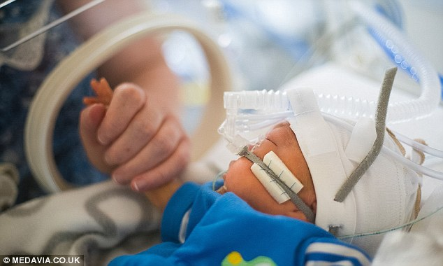 A tender moment as mother and Son hold hands: Saxon was in hospital for five months, with his parents by his side every day