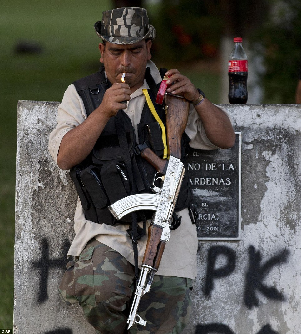 A man belonging to a self-defense group that formed to fight organized crime stands at a checkpoint in Paracuaro