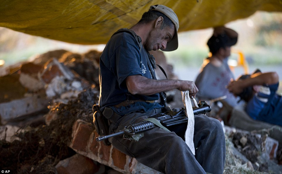 Vigilant: A member of a self-defense group cleans his weapon at a Paracuaro checkpoint