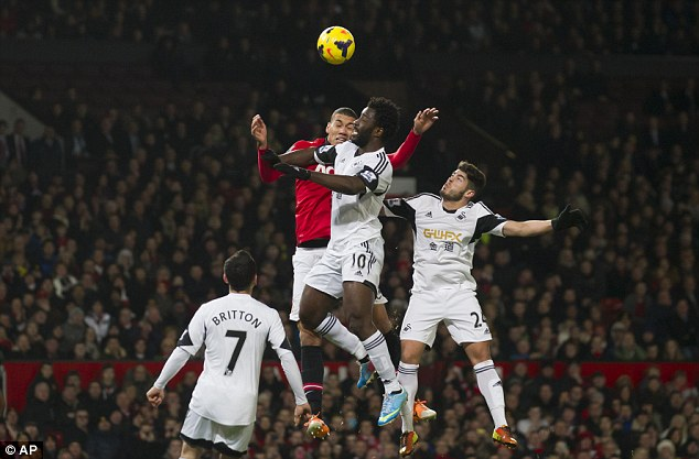 Get up high: Manchester United's Chris Smalling fights for the ball against Wilfried Bony