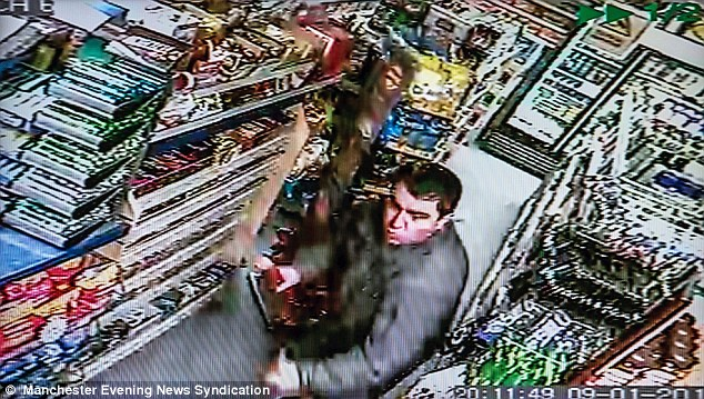 Caught on CCTV: Mr Adineh picks up a piece of wood the chase the crooks off with