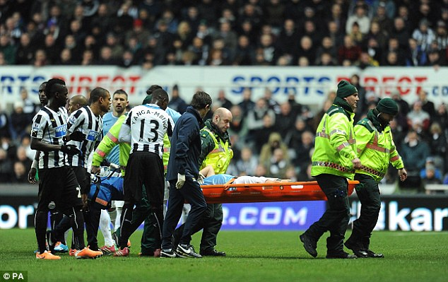 Injured: Nasri is stretchered off after receiving treatment for Yanga-Mbiwa's tackle from behind